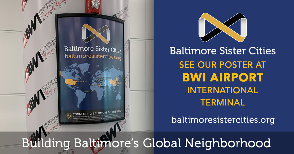 Photo of Baltimore Sister Cities' poster on a pillar at BWI Airport International Terminal. Poster features a map of the world with Baltimore's sister cities and info about Baltimore Sister Cities.